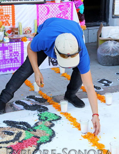 Spreading marigolds in front of a Day of the Dead altar