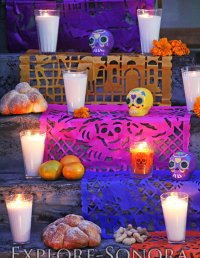 Candles, ceramic skulls and pan de muerto on a Day of the Dead altar