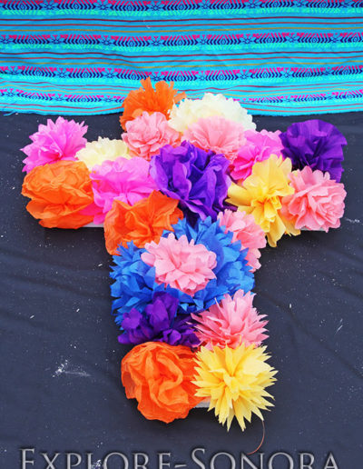 A cross of paper flowers on a Day of the Dead altar